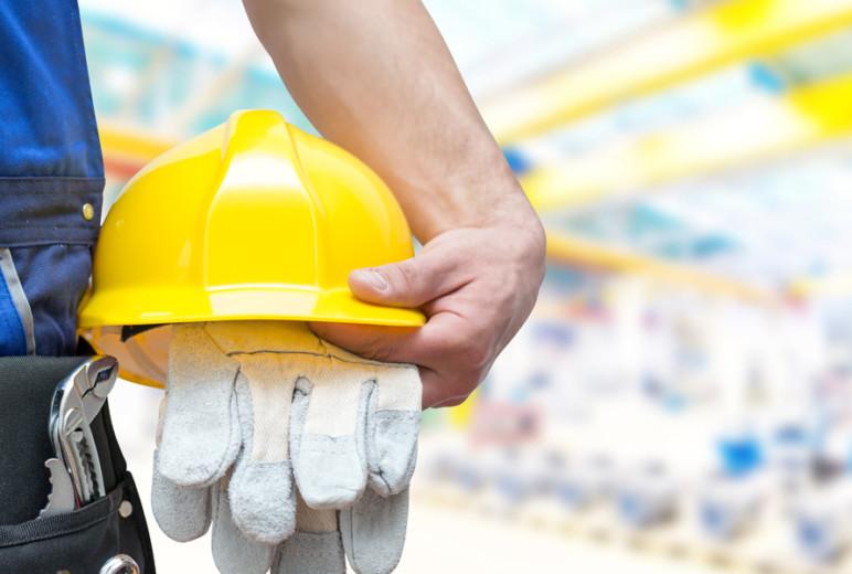Arbeiter mit Werkzeug, Schutzhelm und Schutzhandschuhen